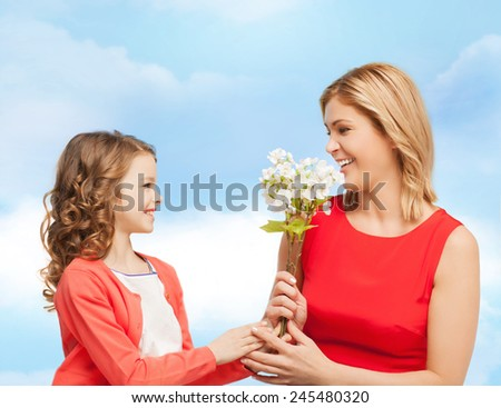 people, holidays, relations and family concept - happy little daughter giving flowers to her mother over blue sky background - stock photo