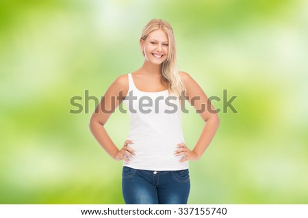 people, holidays, style and body type concept - smiling young woman in blank white shirt and jeans over green natural background - stock photo