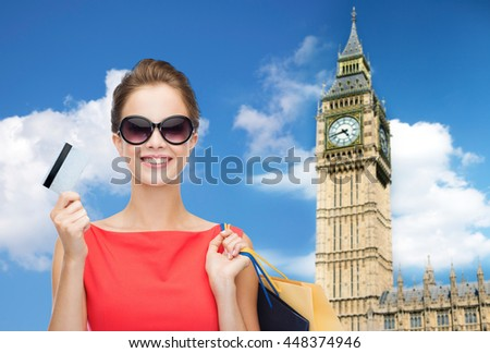 people, holidays, tourism, travel and sale concept - young happy woman with shopping bags and credit card over big ben clock tower background