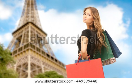 people, holidays, tourism, travel and sale concept - young happy woman with shopping bags over paris eiffel tower background - stock photo