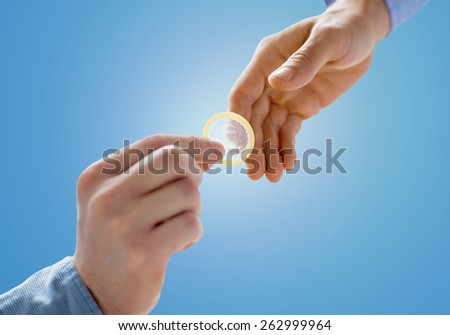 people, homosexuality, safe sex, sexual education and charity concept - close up of happy male gay couple hands giving condom over blue background - stock photo