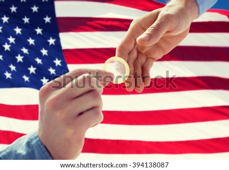 people, homosexuality, safe sex, sexual education and charity concept - close up of male gay couple hands giving condom over american flag background