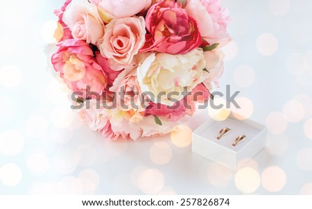 people, homosexuality, same-sex marriage and love concept - close up of gay female wedding rings in little box and flower bunch on table over holiday lights background - stock photo