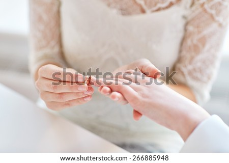 people, homosexuality, same-sex marriage and love concept - close up of happy lesbian couple hands putting on wedding ring - stock photo