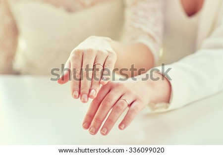people, homosexuality, same-sex marriage and love concept - close up of happy lesbian couple hands showing wedding rings on - stock photo
