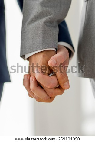people, homosexuality, same-sex marriage and love concept - close up of happy male gay couple holding hands - stock photo
