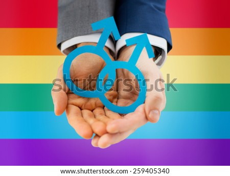 people, homosexuality, same-sex marriage and love concept - close up of happy male gay couple holding paper cutout love symbol over rainbow flag background - stock photo