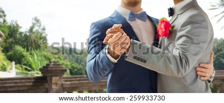 people, homosexuality, same-sex marriage and love concept - close up of happy male gay couple holding hands and dancing on wedding over balcony and nature background - stock photo