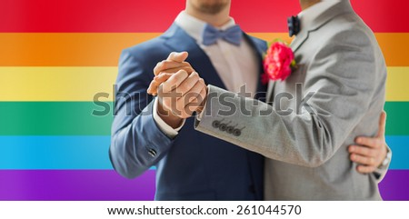 people, homosexuality, same-sex marriage and love concept - close up of happy male gay couple holding hands and dancing on wedding over rainbow flag background - stock photo