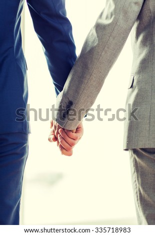 people, homosexuality, same-sex marriage and love concept - close up of happy male gay couple holding hands from back