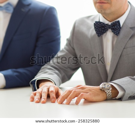 people, homosexuality, same-sex marriage and love concept - close up of happy male gay couple hands on wedding - stock photo