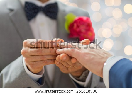 people, homosexuality, same-sex marriage and love concept - close up of happy male gay couple hands putting wedding ring on lights background - stock photo