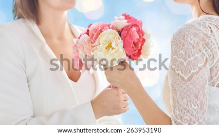 people, homosexuality, same-sex marriage and love concept - close up of happy married lesbian couple with flower bunch over blue holidays lights background