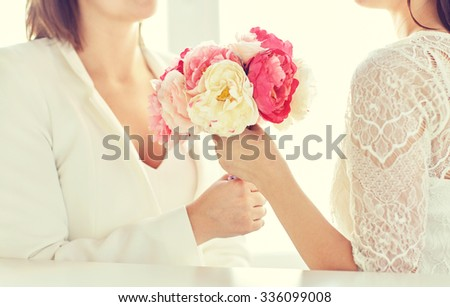 people, homosexuality, same-sex marriage and love concept - close up of happy married lesbian couple with flower bunch - stock photo