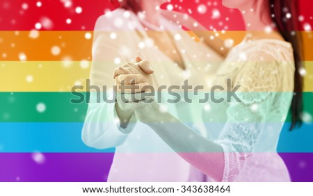people, homosexuality, same-sex marriage and love concept - close up of happy married lesbian couple dancing over rainbow flag stripes background over snow effect - stock photo