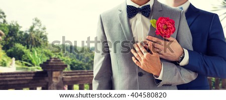 people, homosexuality, same-sex marriage and love concept - close up of happy married male gay couple in suits with buttonholes and bow-ties on wedding over balcony and nature background - stock photo
