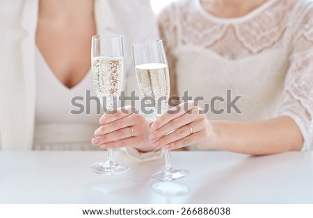 people, homosexuality, same-sex marriage, celebration and love concept - close up of happy married lesbian couple hands holding champagne glasses - stock photo