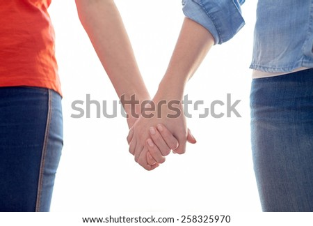 people, homosexuality, same-sex marriage, gay and love concept - close up of happy lesbian couple holding hands