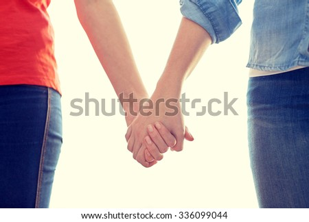people, homosexuality, same-sex marriage, gay and love concept - close up of happy lesbian couple holding hands - stock photo