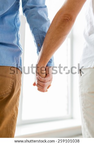 people, homosexuality, same-sex marriage, gay and love concept - close up of happy male gay couple holding hands from back - stock photo