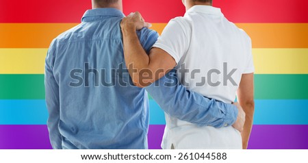 people, homosexuality, same-sex marriage, gay and love concept - close up of happy male gay couple or friends hugging from back over rainbow flag background - stock photo