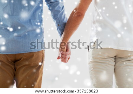 people, homosexuality, same-sex marriage, gay and love concept - close up of happy male gay couple holding hands from back over snow effect - stock photo