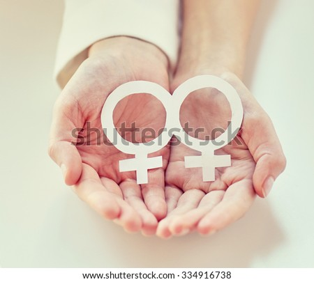 people, homosexuality, same-sex marriage, gay pride and love concept - close up of happy lesbian couple hands holding white paper venus symbol - stock photo