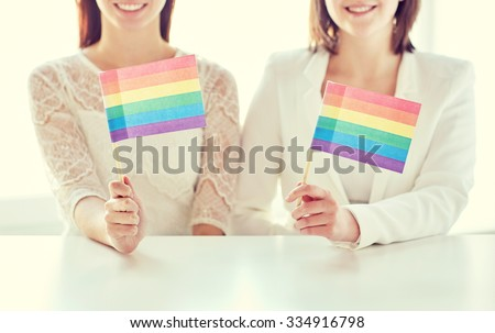 people, homosexuality, same-sex marriage, gay pride and love concept - close up of happy lesbian couple holding rainbow flags - stock photo