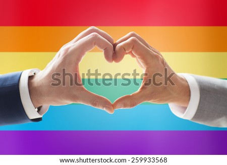people, homosexuality, same-sex marriage, gesture and love concept - close up of happy male gay couple hands showing heart hand sign over rainbow flag background - stock photo
