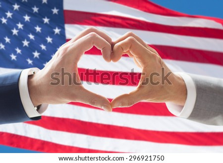 people, homosexuality, same-sex marriage, gesture and love concept - close up of happy male gay couple hands showing heart hand sign over american flag background - stock photo