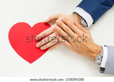 people, homosexuality, same-sex marriage, valentines day and love concept - close up of happy married male gay couple hands with red paper heart shape on table - stock photo