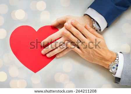 people, homosexuality, same-sex marriage, valentines day and love concept - close up of happy married male gay couple hands with red paper heart shape over holidays lights background - stock photo