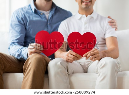 people, homosexuality, same-sex marriage, valentines day and love concept - close up of happy gay male couple with red hearts at home - stock photo