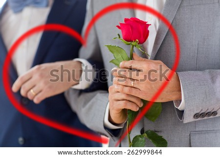 people, homosexuality, same-sex marriage, valentines day and love concept - close up of happy male gay couple with red rose flower holding hands on wedding with red heart shape - stock photo