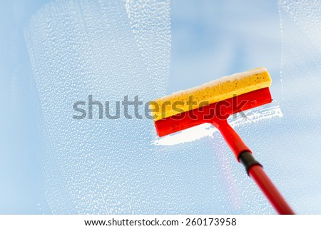 people, housework and housekeeping concept -close up of hand cleaning window glass with sponge mop and foam - stock photo