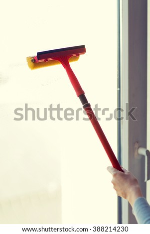 people, housework and housekeeping concept -close up of hand cleaning window with sponge mop - stock photo