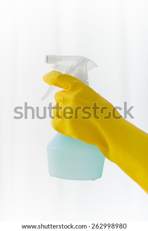 people, housework and housekeeping concept - close up of hand with cleanser spraying home