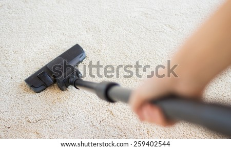 people, housework and housekeeping concept - close up of hand with vacuum cleaner cleaning carpet at home - stock photo