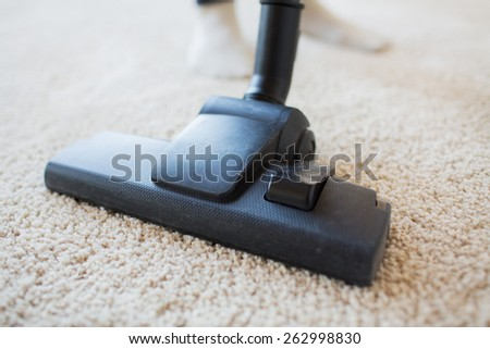 people, housework and housekeeping concept - close up of vacuum cleaner nozzle cleaning carpet at home - stock photo