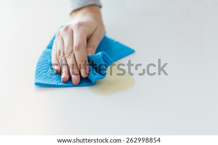 people, housework and housekeeping concept - close up of woman hand cleaning spot from table surface with cloth at home - stock photo