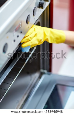 people, housework and housekeeping concept - close up of woman hand in protective glove with rag cleaning oven at home kitchen - stock photo