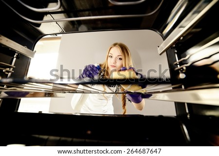 people, housework and housekeeping concept - close up of woman hand in protective glove with rag cleaning oven at home kitchen. View from the interior of the oven
