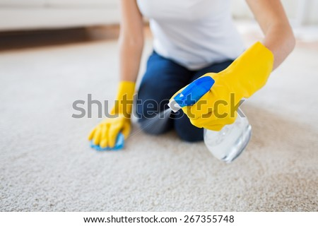 people, housework and housekeeping concept - close up of woman in rubber gloves with cloth and derergent spray cleaning carpet at home - stock photo
