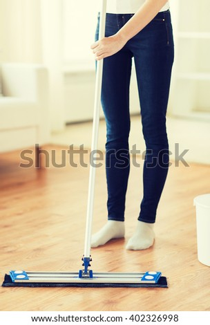people, housework and housekeeping concept - close up of woman legs with mop cleaning floor at home - stock photo