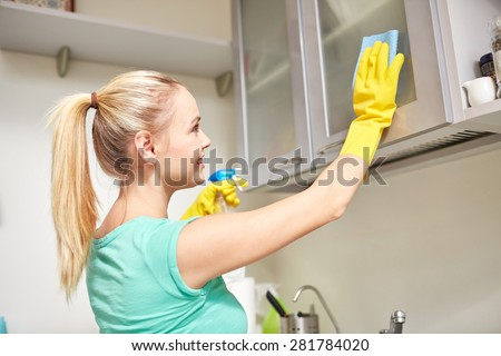 people, housework and housekeeping concept - happy woman cleaning cabinet with rag and cleanser at home kitchen - stock photo