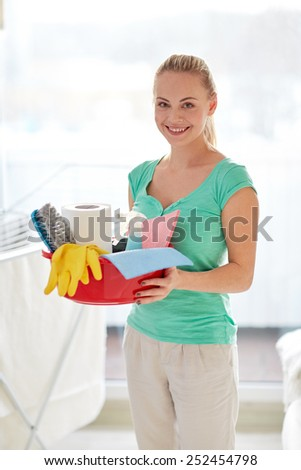 people, housework and housekeeping concept - happy woman holding cleaning stuff at home - stock photo