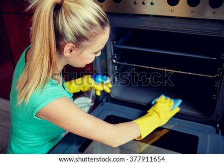 people, housework and housekeeping concept - happy woman with bottle of spray cleanser cleaning oven at home kitchen - stock photo