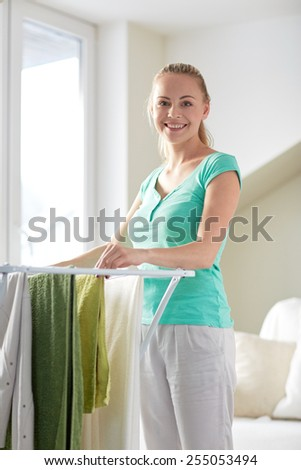 people, housework, laundry and housekeeping concept - happy woman hanging clothes on dryer at home - stock photo