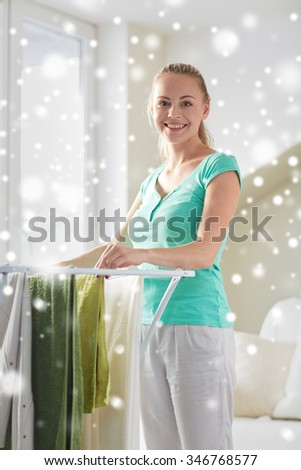 people, housework, laundry and housekeeping concept - happy woman hanging clothes on dryer at home over snow effect