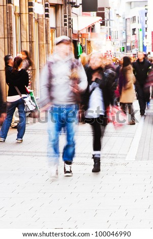 people imaged in motion blur walking in the city - stock photo